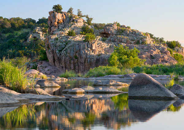 Stock photo of sunset behind large rock formations along the Llano River in the Texas Hill Country
