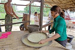 Woman Sifting Crushed Rice