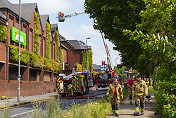Smoke continues to rise from roof timbers where Firefighters use an aerial platform to attack the last few pockets of fire at The Mall in Walthamstow in North East London, that broke out during rush hour this morning and appears to have destroyed the foodcourt and according to a manager escorted by LFB officials at the adjacent Asda, a large amount of stock. London, July 22 2019.