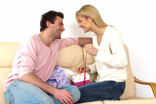 couple sitting on a sofa opening a present<br />