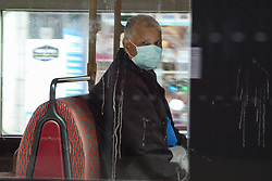 © Licensed to London News Pictures. 13/06/2020. London, UK. A man wearing a face covering travels on a London bus. Face covering will be compulsory on buses, trains, trams and planes from Monday 15 June. Secretary of State for Transport, Grant Shapps has said that, people who do not wear face covering on public transport from Monday could be fined up to £100. Photo credit: Dinendra Haria/LNP