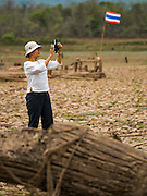 02 APRIL 2016 - NA SAK, LAMPANG, THAILAND: A Thai woman uses her smart phone to photograph the ruins of Sobjant village. The village of Sobjant in Na Sak district in Lampang province was submerged when the Mae Chang Reservoir was created in the 1980s. The village was relocated to higher ground a few kilometers from its original site. The drought gripping Thailand drained the reservoir and the foundations of the Buddhist temple in the original village became visible early in 2016. Thai families come down to the original village to pray in the ruins of the temple and look at what's left of the village. This is the first time in more than 30 years that this area has not been under two meters of water.      PHOTO BY JACK KURTZ