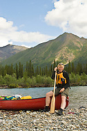 A canoeist takes a break on the Wind River, Yukon.<br /> <br /> NOT IN YOUR BUDGET? Contact Cathie for a price specific to your project.