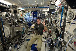 French cosmonaut Thomas Pesquet reads a book with a floating earth globe, during a tele-conference on board International Space Station, on December 24, 2016. Photo by ESA via Balkis Press/ABACAPRESS.COM