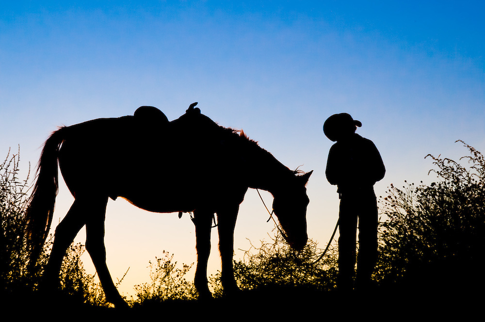 Image of a young cowboy and his horse at sunset. Silhouette of boy and a horse. Lifestyle photograph mood of old west or country boy for Carole Jones Commercial Photography portfolio.