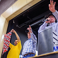 Auctioneers Wayne Connell and Delbert Autry all out bids on a rug held by Danny Yazzie during the monthly Crownpoint Rug Auction at Crownpoint Elementary School April 8.