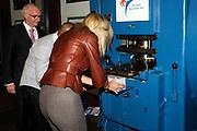 """Prinses Máxima slaat eerste munt 'Week van het geld'<br /> <br /> Hare Koninklijke Hoogheid Prinses Máxima der Nederlanden heeft op donderdagmiddag 10 november 2011 de eerste 'Week van het geld'-munt bij de Koninklijke Nederlandse Munt in Utrecht. De vormgeving van de munt is het resultaat van een ontwerpwedstrijd onder basisscholen in Nederland. De munt is geen wettig betaalmiddel. <br /> <br /> <br /> Princess Maxima attends first coin 'Money Week'<br /> <br /> Her Royal Highness Princess Máxima of the Netherlands attends on Thursday 10 November 2011 the first """"Week of money' coin at the Royal Dutch Mint in Utrecht. The design of the coin is the result of a design competition among primary schools in the Netherlands. <br /> <br /> Op de foto / On the photo : <br />  Prinses Maxima"""