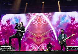 © Licensed to London News Pictures. 12/06/2015. Newport, UK.   You Me at Six  performing live at Isle of Wight Festival 2015, Day 2 Friday.  In this picture - Josh Franceschi (left), Matt Barnes (right).  This afternoon has seen torrential downpours of rain after the last day of hot sunshine.   Photo credit : Richard Isaac/LNP