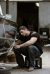 very good looking muscular auto mechanic with grease and dirt on his face working on a classic car