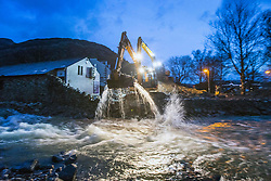 © Licensed to London News Pictures. 10/12/2015. Glenridding UK. Diggers are trying to clear the beck of rocks in The village of Glenridding in Cumbria that has flooded for a second time this week after the beck broke it's banks. Photo credit: Andrew McCaren/LNP
