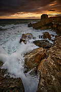 Pulpit Rock, Portland Bill, at sunset under a stormy sky. The rising tide causes waves to break over the foreground rocks.