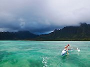 Men paddling in a canoe in the shallow water off the O'Ahu coast, Hawai?i