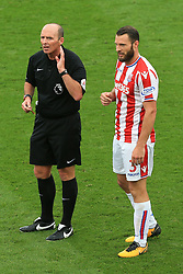 23rd September 2017 - Premier League - Stoke City v Chelsea - Referee Mike Dean struggles to hear something from the sidelines as Erik Pieters of Stoke looks on confused - Photo: Simon Stacpoole / Offside.