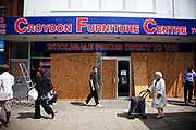 The day after rioting took place in Croydon in South London the Croydon Furniture Centre boards up it's broken windows. Riots flared for a third night in a row, resulting in burnt out buildings, looted shops and general smashed up devastation.