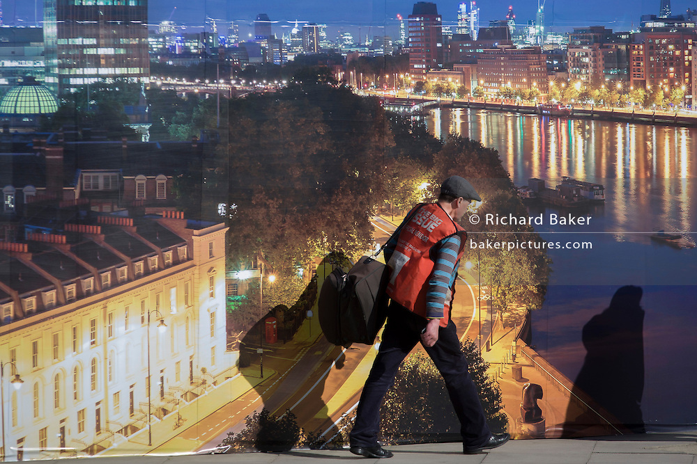 A Big Issue seller walks past a property company's construction hoarding, a night time panorama of  Thames riverside properties.