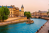 People relaxing on the banks of the RIver Seine in springtime with Pont Saint-Michel (bridge) in background, Paris, France.