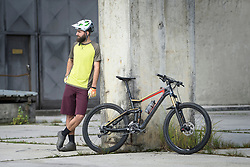 Mountain biker stands close to his bike in city