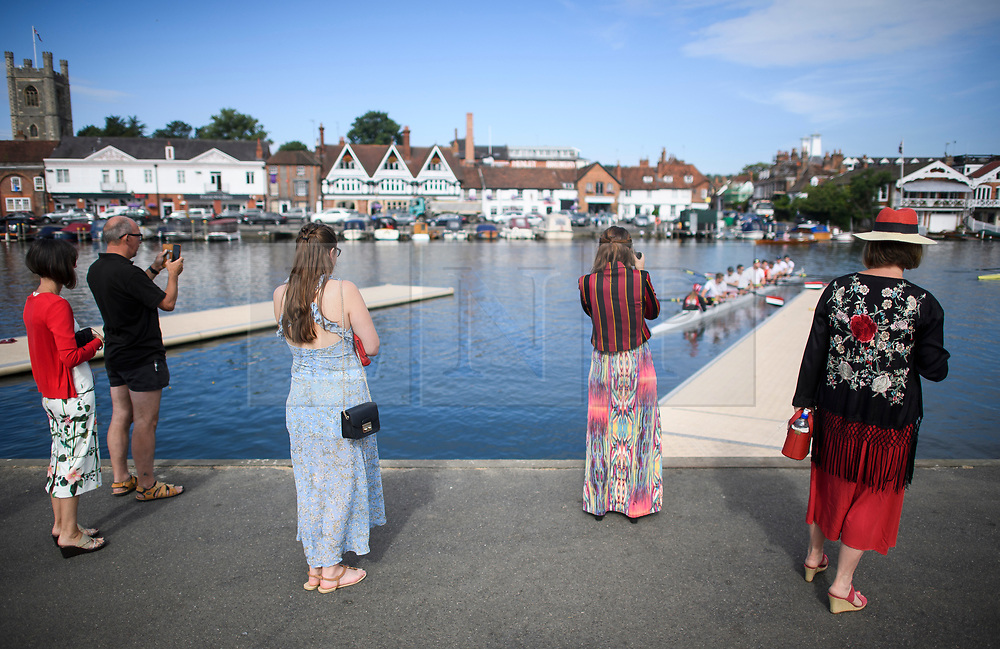 © Licensed to London News Pictures. 04/07/2018. Henley-on-Thames, UK. A group of women watch as a team takes to the water on day one of the Henley Royal Regatta, set on the River Thames by the town of Henley-on-Thames in England. Established in 1839, the five day international rowing event, raced over a course of 2,112 meters (1 mile 550 yards), is considered an important part of the English social season. Photo credit: Ben Cawthra/LNP