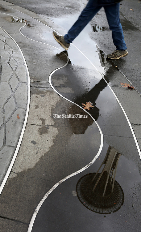 The Space Needle is reflected in one of Seattle Center's many puddles during a break in the rain in Seattle.<br /> <br /> Ken Lambert / The Seattle Times