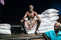 Kandy, Sri Lanka -- January 31, 2018: A worker at a local fresh market, taking a break from unloading bags of grain.