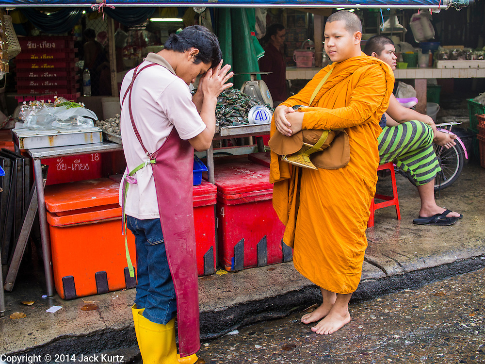 19 NOVEMBER 2014 - BANGKOK, THAILAND: A market vendor prays with a Buddhist monk and offering alms to make merit in Khlong Toei Market in Bangkok. Between July and September the economy expanded 0.6 percent compared to the previous year, the National Economic and Social Development Board (NESDB) reported. Thailand's economy achieved a weak 0.2 per cent growth across the first nine months of the year. The NESDB said the Thai economy is expected to grow by 1 percent in 2014. Authorities say the sluggish growth is because tourists have not returned to Thailand in the wake of the coup in May, 2014, and that reduced demand for computer components, specifically hard drives, was also hurting the economy. Thailand is the leading manufacturer of computer hard drives in the world. The Thai government has announced a stimulus package worth $11 billion (US) to provide cash handouts to farmers and promised to speed up budget spending to boost consumption.   PHOTO BY JACK KURTZ