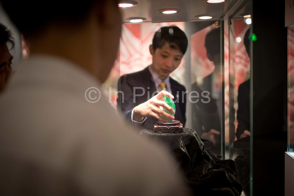 """A staff places a work of jade into a display case during a public preview after a press conference announcing Christie's very first mainland China auction in Shanghai, China September 23,  2013. Both Southeby's and Christie's have opened an office in Mainland China in the past year, however they face overwhelming odds as China's state-owned auction houses such as Poly and Jiamu enjoys a near monopoly over China's art procurement market as foreigners are not allowed to buy vaguely defined """"historical"""" art."""