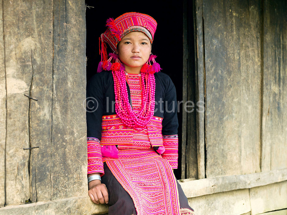 Portrait of Porpae, an unmarried Ko Pala ethnic minority girl wearing her traditional costume at home, Ban Honglerk, Phongsaly Province, Lao PDR. The brightly coloured, flamboyant costumes of the young Pala women are in contrast to the more conservative clothing of their elders. One of the most ethnically diverse countries in Southeast Asia, Laos has 49 officially recognised ethnic groups although there are many more self-identified and sub groups. These groups are distinguished by their own customs, beliefs and rituals. Details down to the embroidery on a shirt, the colour of the trim and the type of skirt all help signify the wearer's ethnic and clan affiliations.