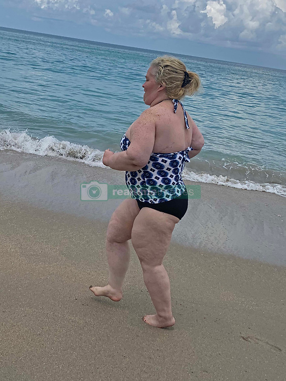 """EXCLUSIVE: Mama June jogs on a beach in a swimsuit as she ramps up her weight loss campaign. The reality star, 40, is determined to lose 45lbs and has been doing yoga sessions and long walks to try and meet her weight goal. The mother-of-four was pictured at Jensen Beach, Florida where she showed off her new keep fit plan. A friend, who revealed June has lost 20lbs so far, said: """"June has really been focusing on her fitness to try and shed some of the pounds she put on. She's been doing a lot of yoga and jogging in the mornings on the beach. """"She has been training everyday with her close friend artist Adam Barta."""" June once weighed 460lbs but lost a staggering 300lbs after an intense exercise regime coupled with gastric and plastic surgery. Since tipping the scales at 160lbs she has now put on some extra weight and is bidding to lose an extra 45lbs. She is pictured wearing a swimsuit gifted to her by Dominique's surf shop in Florida. 02 Jun 2020 Pictured: Mama June jogs on a beach in a swimsuit as she ramps up her weight loss campaign. Photo credit: MEGA TheMegaAgency.com +1 888 505 6342"""