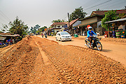 09 MARCH 2013 - ALONG HIGHWAY 13, LAOS:  Motorists make their way past a construction zone on Highway 13 near the Lao capital of Vientiane. The paving of Highway 13 from Vientiane to near the Chinese border has changed the way of life in rural Laos. Villagers near Luang Prabang used to have to take unreliable boats that took three hours round trip to get from the homes to the tourist center of Luang Prabang, now they take a 40 minute round trip bus ride. North of Luang Prabang, paving the highway has been an opportunity for China to use Laos as a transshipping point. Chinese merchandise now goes through Laos to Thailand where it's put on Thai trains and taken to the deep water port east of Bangkok. The Chinese have also expanded their economic empire into Laos. Chinese hotels and businesses are common in northern Laos and in some cities, like Oudomxay, are now up to 40% percent. As the roads are paved, more people move away from their traditional homes in the mountains of Laos and crowd the side of the road living off tourists' and truck drivers.    PHOTO BY JACK KURTZ