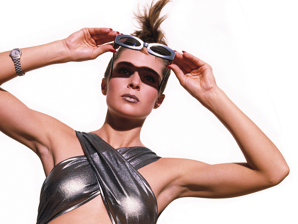 Woman in silver crisscrossed bathing suit holding sunglasses and looking at the sun. She has an exotic hair style and is standing in front of a white background and photo is cropped under her breasts.