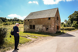 A man looks around near Seagram's Farm in Imber village on Salisbury Plain, Wiltshire, where residents were evicted in 1943 to provide an exercise area for US troops preparing to invade Europe. Roads through the MoD controlled village are now open and will close again on Monday August 22.