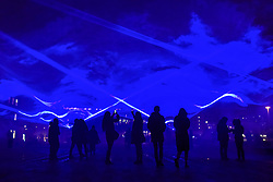 """© Licensed to London News Pictures. 17/01/2018. LONDON, UK. People view """"Waterlicht"""" by Daan Roosegaarde in Granary Square, Kings Cross.  Preview of Lumiere London, the capital's largest arts festival commissioned by The Mayor of London and produced by Artichoke.  Light installations by leading artists have been set up, both north and south of the river for the public to view 18-21 January.   Photo credit: Stephen Chung/LNP"""