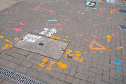 Colourful markings on the pavement on 5th August 2020 in Birmingham, United Kingdom. These spray painted marks are made by utility companies who are marking out where wires and pipes go underneath street level. The marks help to inform different workers when roadworks or other repairs are being undertaken.