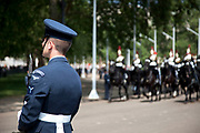 The Blues and Royals approach as a member of the RAF Regiment stands guard. Royal procession for the State Opening of Parliament, London. This procession takes Queen Elizabeth to parliament to deliver the Queen's Speech.