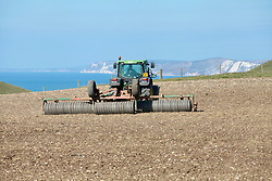 Covid 19 - Tractor working a field in Dorset dried by a key worker during the movement restrictions. UK April 2020