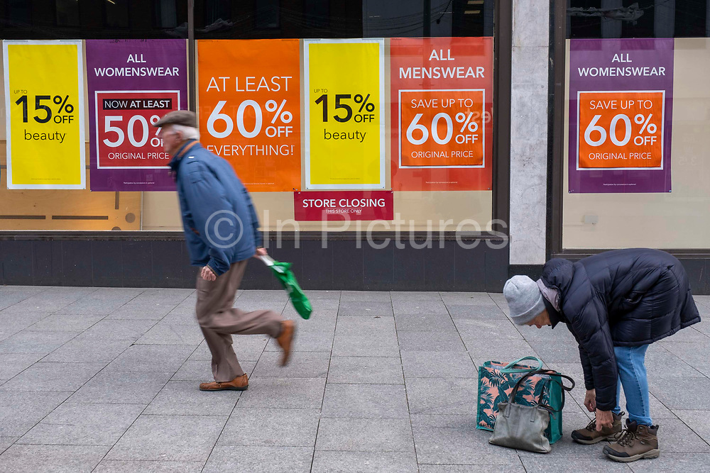 People walking past the sale signs outside the Folkestone Debenhams store in the final few days of the 'Everything Must Go' sale before closing down on 13th Jauary 2020 in Folkestone, Kent. United Kingdom. The company announced the closure of 19 stores across the UK after going into administration in 2019.