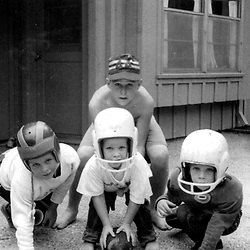 HS636   George W. (playing quarterback), Jeb, and Neil Bush play football with a friend, Houston, TX,<br /> Fall 1959.<br /> Photo Credit:  George Bush Presidential Library