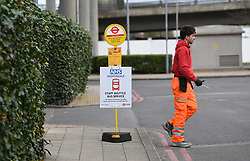 A workman by a stop for the staff shuttle bus service near the ExCel centre in London which is being made into the temporary NHS Nightingale hospital to help tackle coronavirus.