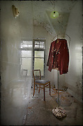 A jacket hanging on a stand in a bathroom at the abandoned Potters Manor.