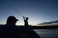Dan Bierman of Victor casts his line on the Teton River as T.R. Raferty pilots the driftboat during an evening float in Teton Valley, Idaho.
