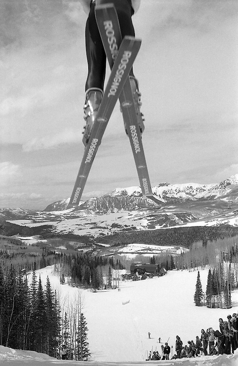 A gallende jumper crosses the tails of his skis as he soars over the Misty Maiden slope in Telluride, CO, just above Goronno Lodge.