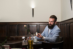 Well-dressed man looking at watch while sitting at restaurant