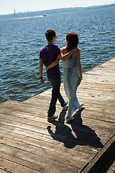 United States, Washington, Kirkland.  couple walking on pier on Lake Washington with boat and Seattle in distance.  MR