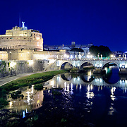 ROME, Italy - The lights of the Castel Sant'Angelo and the bridge next to it are reflected on the still waters of the Tiber in Rome, Italy.