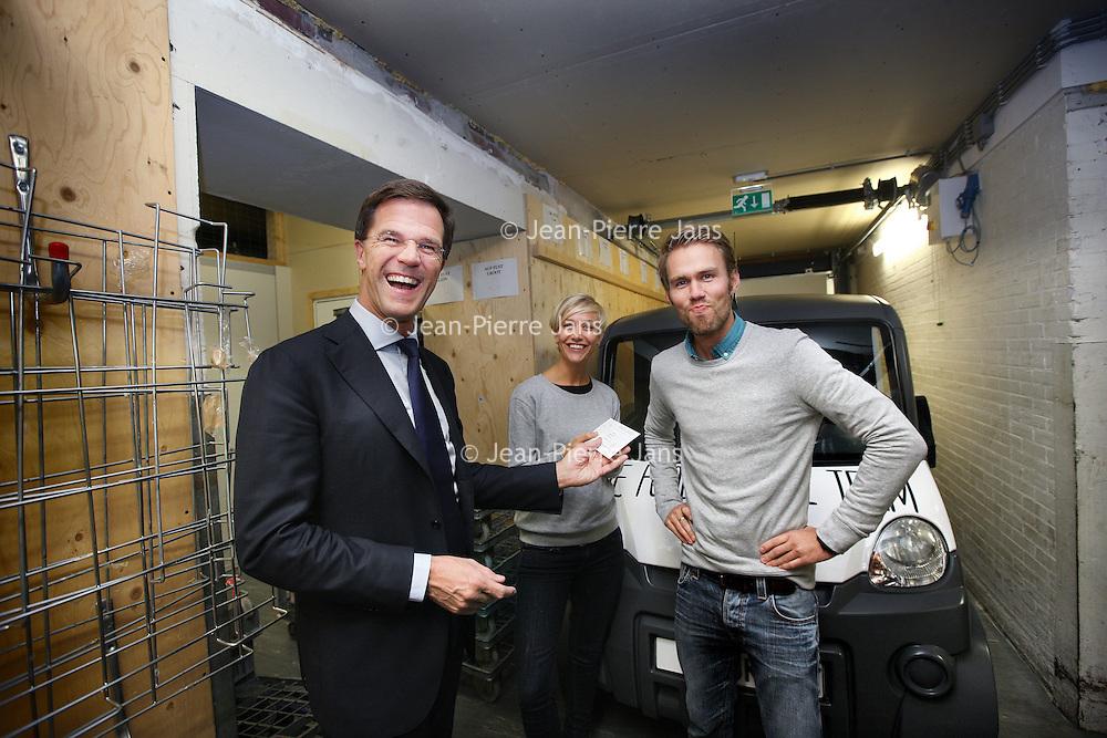 Nederland, Amsterdam , 30-10-2014.<br /> Bedrijfsbezoek van minister-president Mark Rutte op uitnodiging van Ahold/Albert Heijn aan Albert Heijn filiaal in de Molukkenstraat in Amsterdam Oost.<br /> Op de foto: Mark Rutte krijgt een diner bon van Ahold medewerkers die z.g. overdatum producten van AH leveren aan een restaurant die daar vervolgens weer lekkere maaltijden van maakt.<br /> <br /> <br /> Foto:Jean-Pierre Jans/ANPinOpdracht