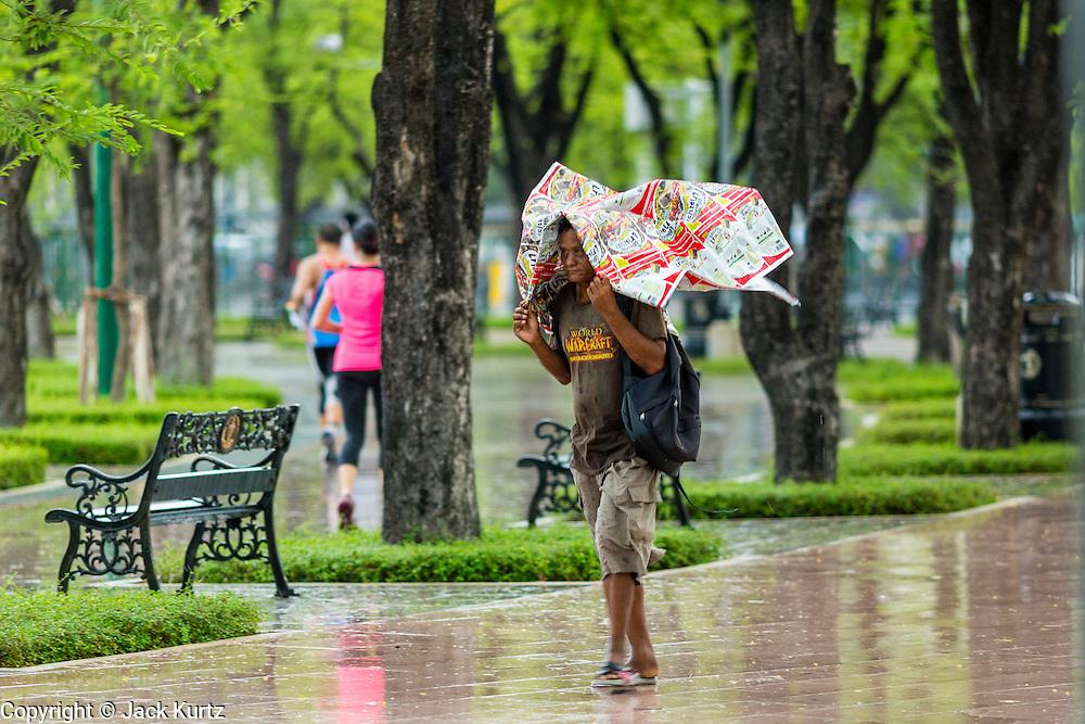 05 MAY 2013 - BANGKOK, THAILAND:  A homeless man walks around Sanam Luang (the royal parade ground) during an unseasonal thunderstorm near the Grand Palace in Bangkok, Thailand. The rainy season in Bangkok is usually mid June through early November, but 2013 has seen unseasonal rains through what is normally Bangkok's dry season.       PHOTO BY JACK KURTZ