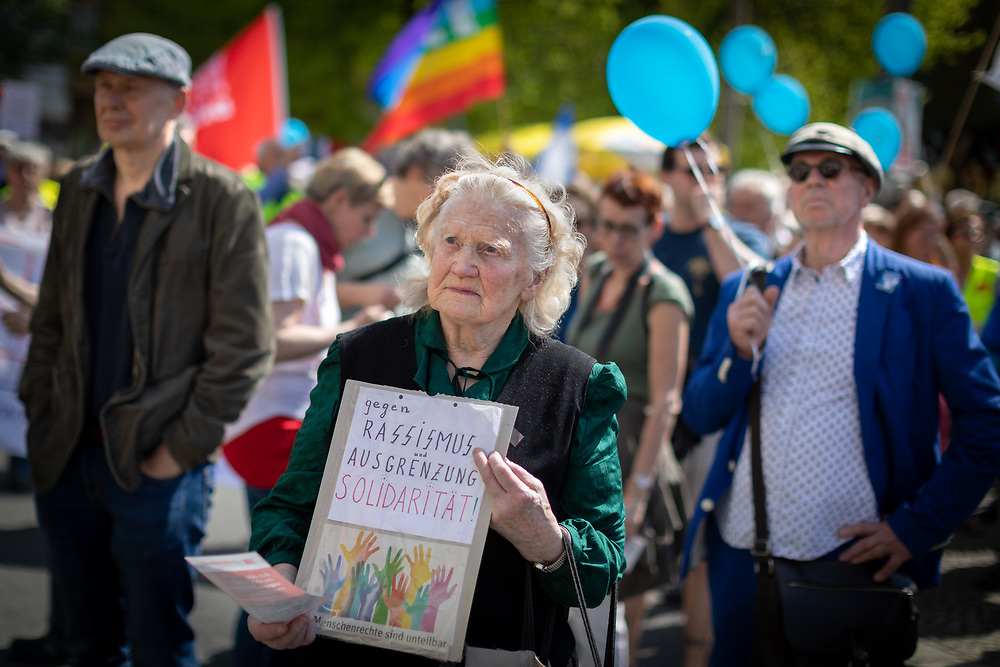 """Mehrere hundert Menschen beteiligen sich am Karsamstag am traditionellen Ostermarsch der Friedensbewegung unter dem Motto """"Abrüsten statt Aufrüsten - Die Welt braucht Frieden statt Kriegsbündnisse"""" in Berlin und protestieren gegen Krieg, Waffenexporte, die NATO.<br /> Demonstrantin mit Schild: gegen Rassismus und Ausgrenzung Solidarität!<br /> <br /> [© Christian Mang - Veroeffentlichung nur gg. Honorar (zzgl. MwSt.), Urhebervermerk und Beleg. Nur für redaktionelle Nutzung - Publication only with licence fee payment, copyright notice and voucher copy. For editorial use only - No model release. No property release. Kontakt: mail@christianmang.com.]"""