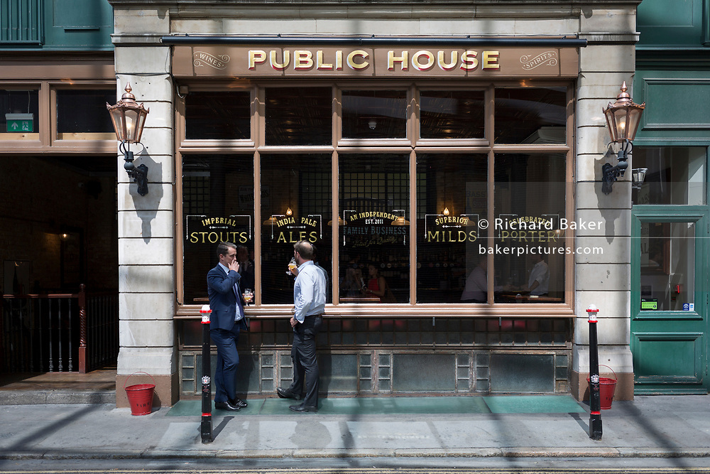 Two afternoon drinkers stand outside a public house (pub) enjoying cool beers on a hot day in the Square Mile, the capital's ancient financial district dating back to the 1st century Roman era, on 17th Juy 2017, in the City of London, England.