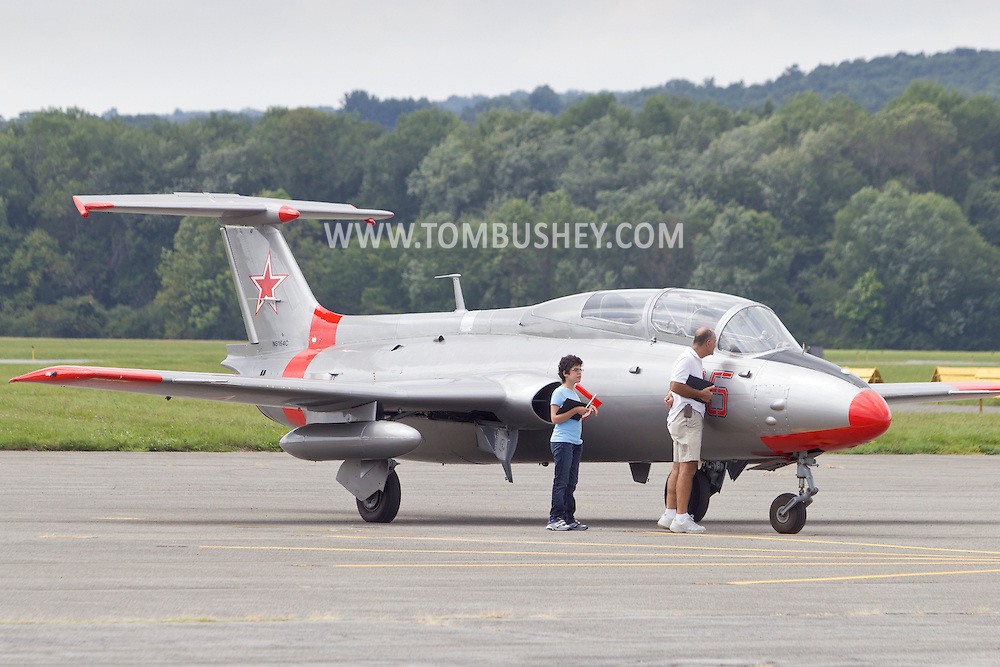 Montgomery, New York - A man looks into the cockpit on an Aerovodochody L-29 Delfin on display during the Experimental Aircraft Association (EAA) Chapter 501 fly-in at Orange County Airport on Sept. 8, 2012. The jet was built in Czechoslovakia as a military trainer.