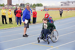Judge and young wheelchair user taking part in Mini games sports event held at Stoke Mandeville Stadium,